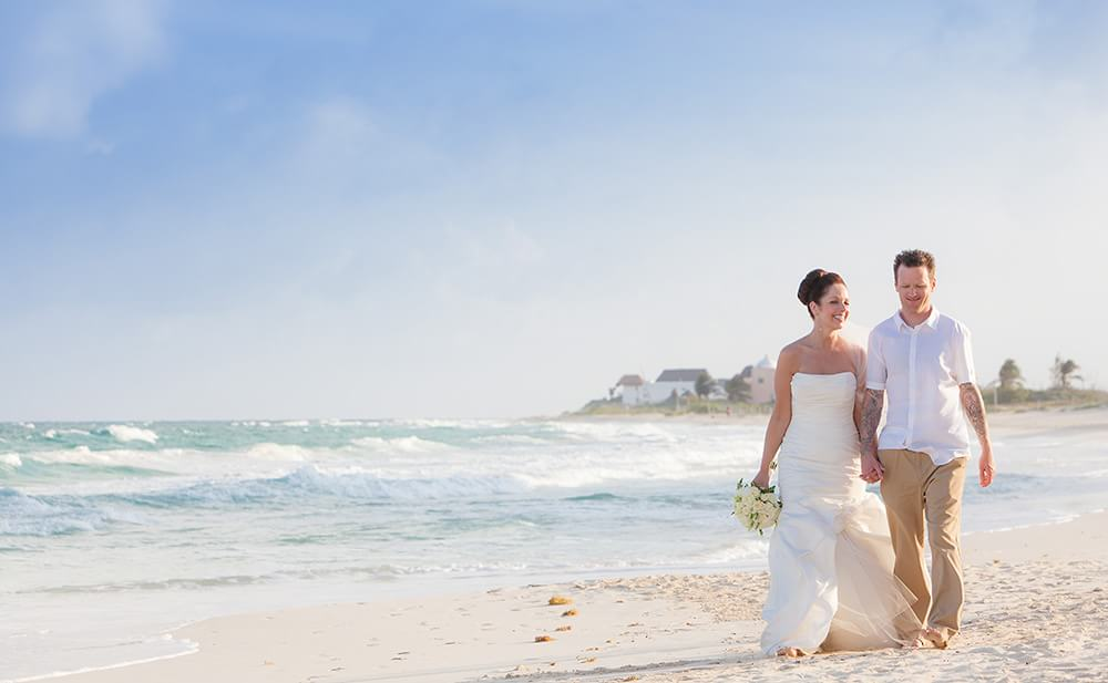 Wedding couple walking down beach in Riviera Maya