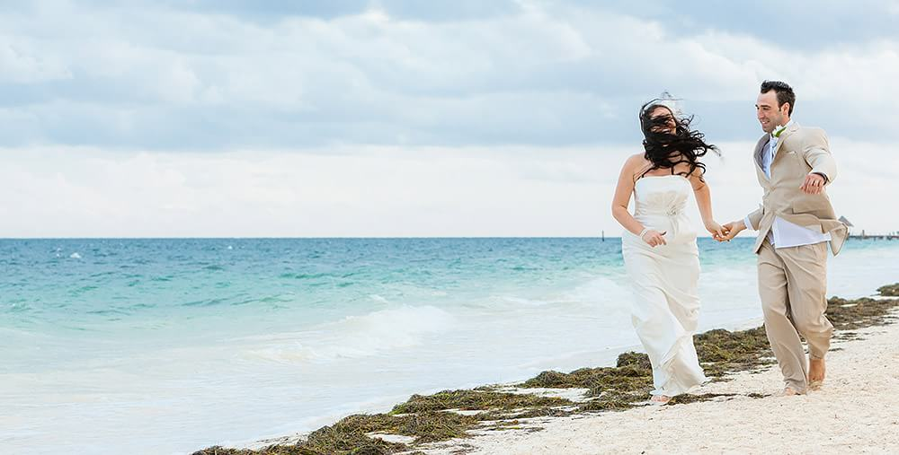 Bride running down beach in Cancun with hair in her face.