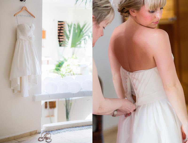Brides mother helping bride put on dress before wedding