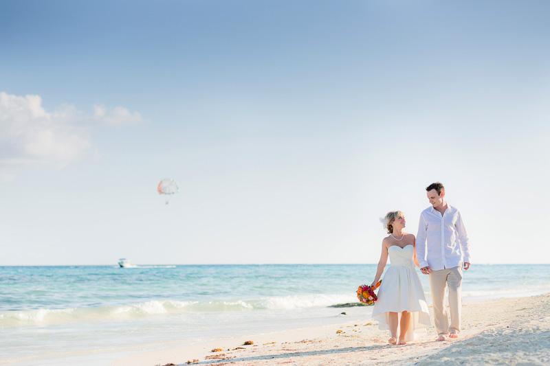 Bride and groom walking on beach in Playa del Carmen