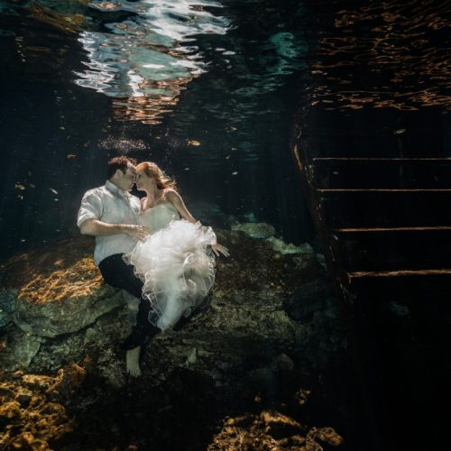 bride and Groom about to kiss in underwater trash the dress in Mayan Cenote at Riviera Maya
