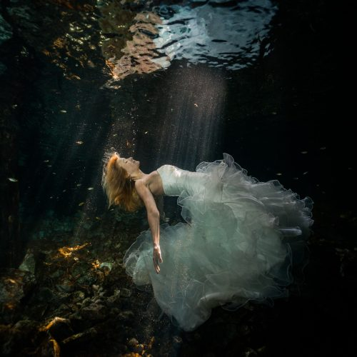 Bride floating to the surface in underwater trash the dress in Mayan Cenote at Riviera Maya