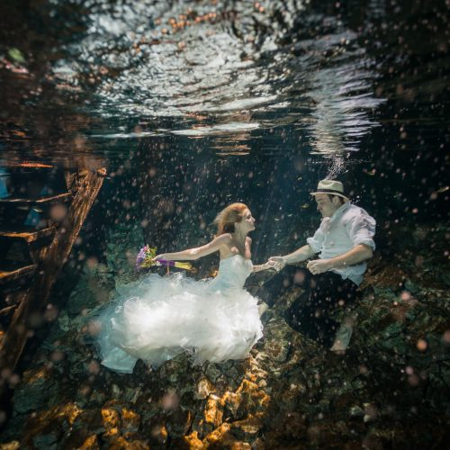 bride and Groom holding hands in underwater trash the dress in Mayan Cenote at Riviera Maya