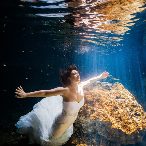 Bride swimming to the surface with her arms extended in Mayan Cenote , Riviera Maya