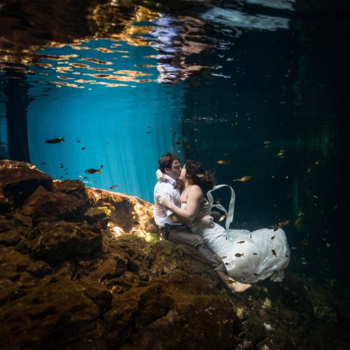 Bride and groom kissing in underwater trash the dress in Mayan Cenote , Riviera Maya