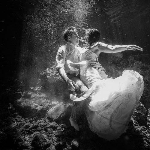 Black and white phoograph of groom and bride kissing in underwater Trash the dress in Mayan Cenote at Riviera Maya