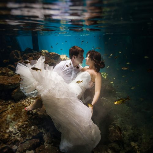 Bride and Groom about to kiss in underwater trash the dress session in Mayan Cenote at Riviera Maya