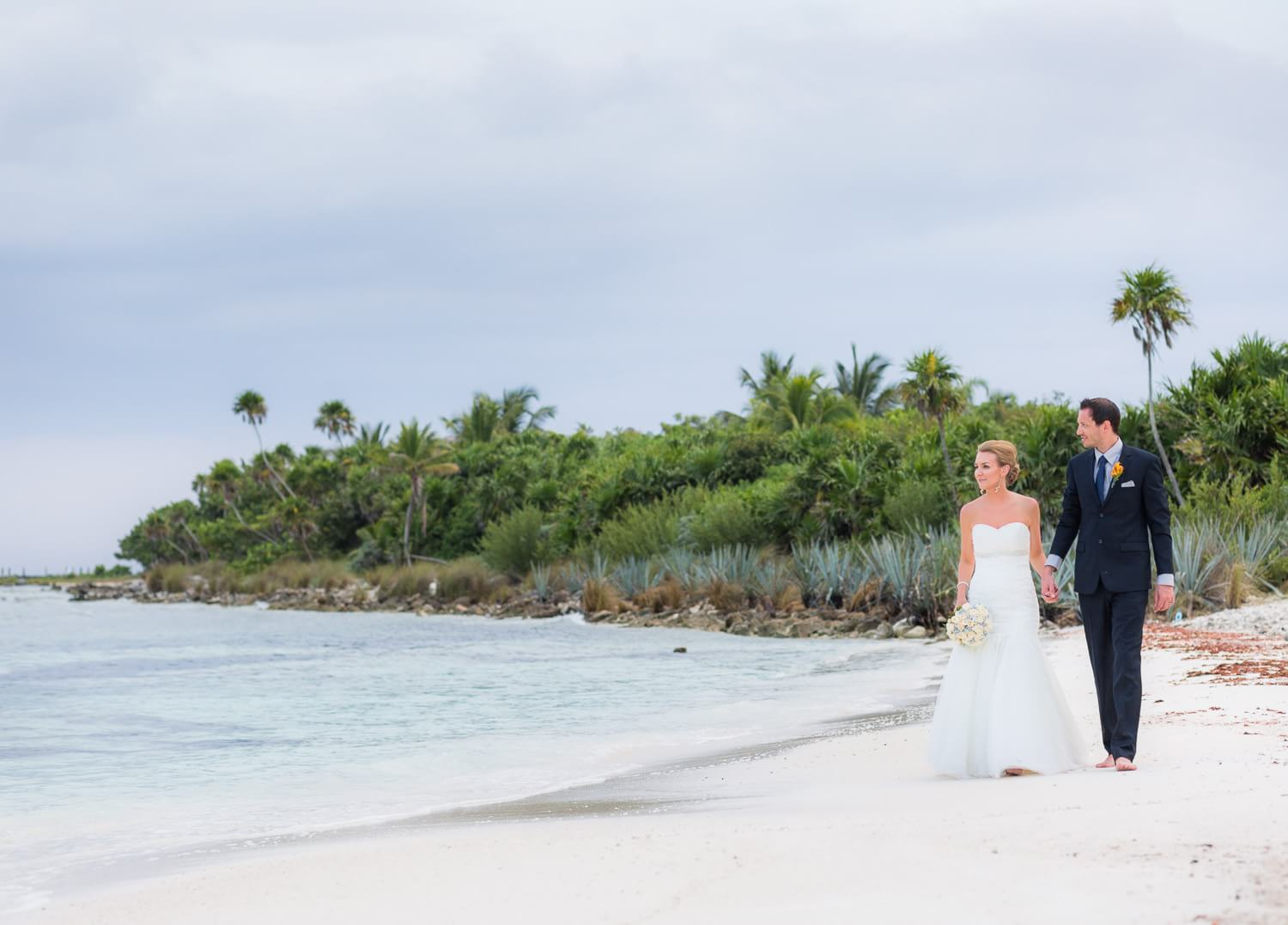 Ashely and Josh walking on beach at their Mexico wedding.