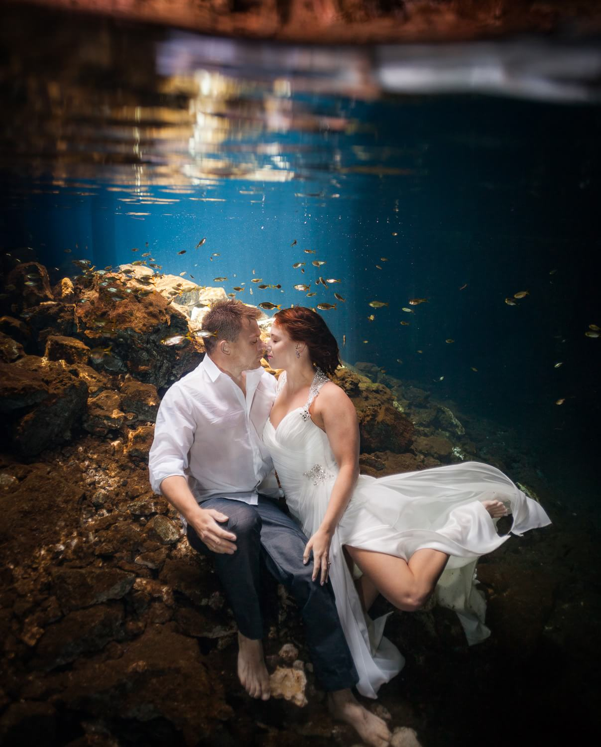 Couple kissing underwater in Mayan Cenote Trash the Dress