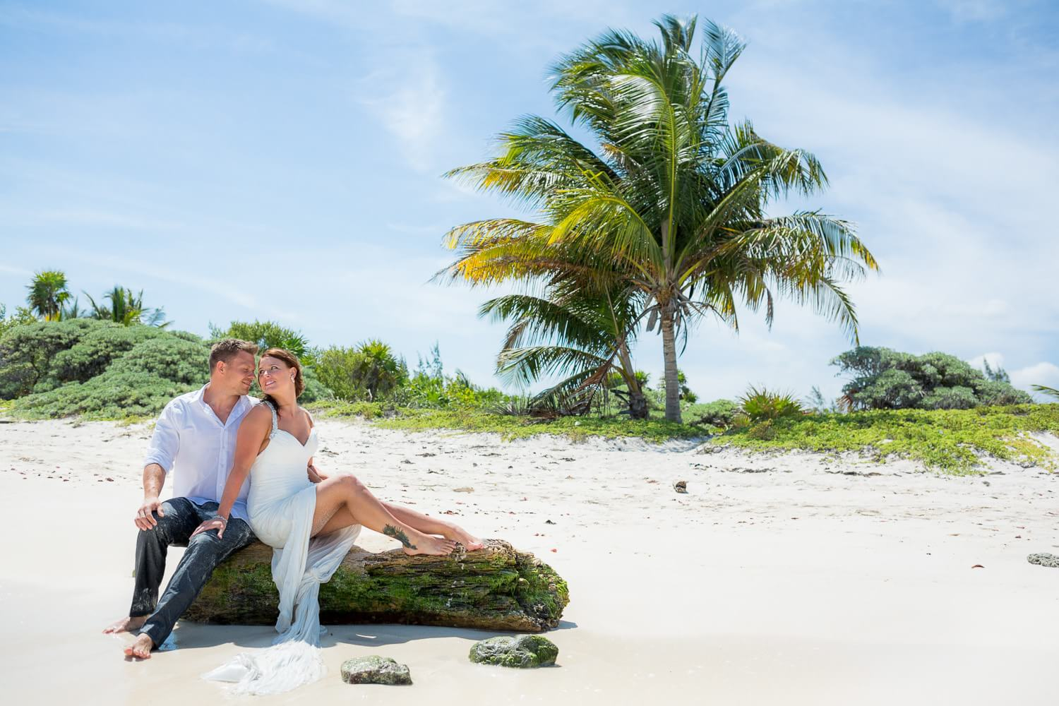 Couple kissing on beach on log in Riviera Maya