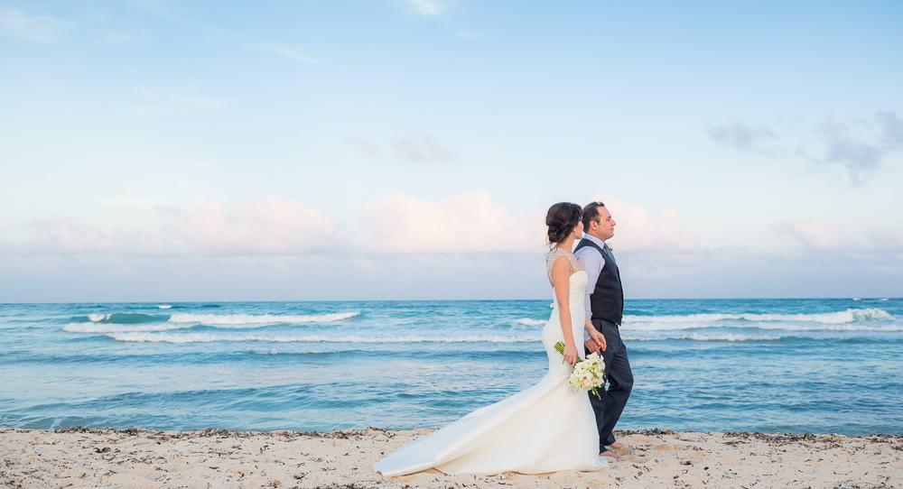 Couple walking on beach at Tulum wedding