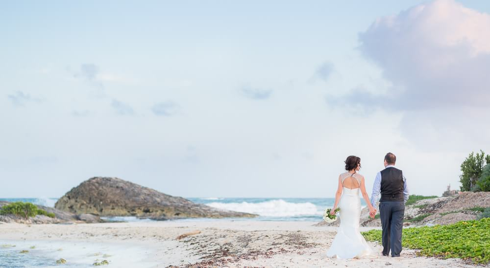 Couple walking down beach by Tulum wedding photographer