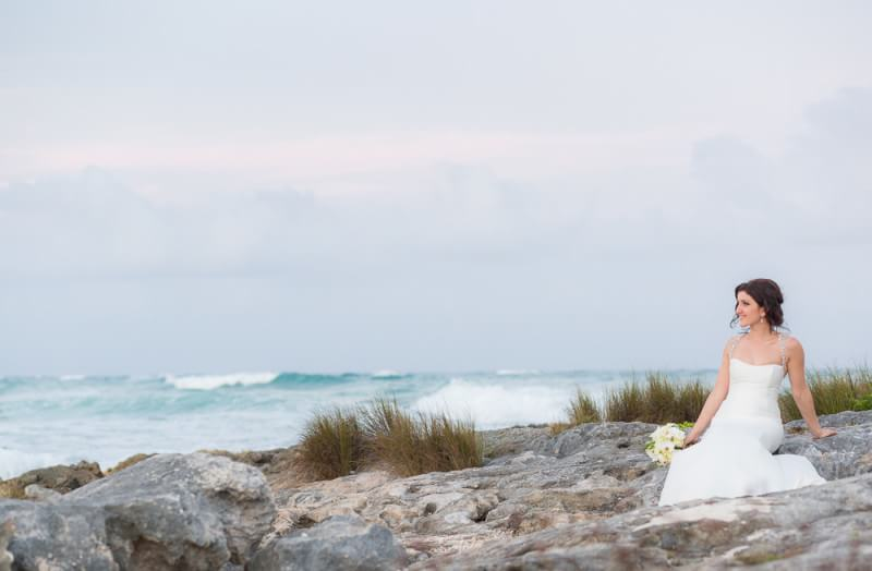 Bride sitting on rocks in Tulum