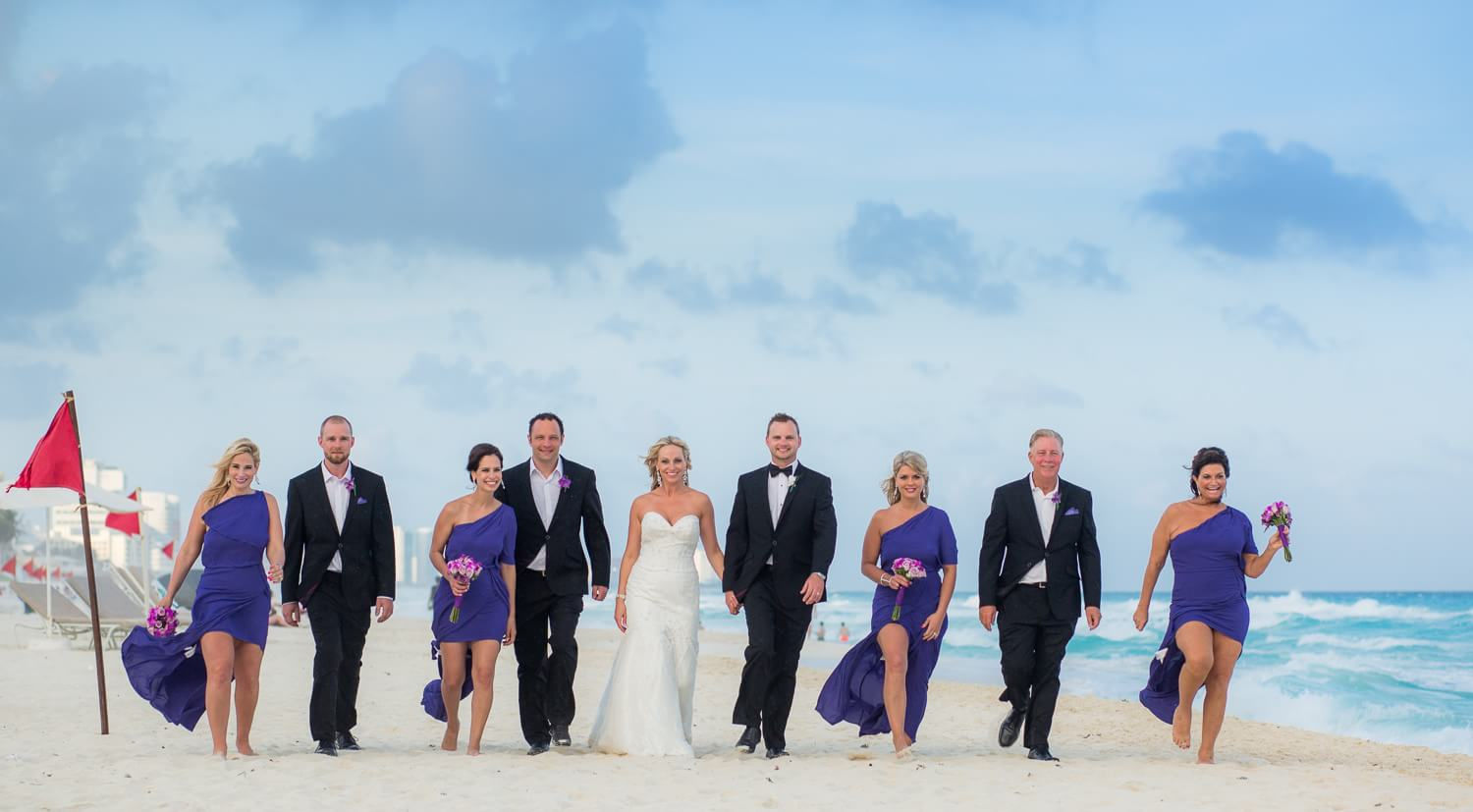Bridal party walking down beach at cancun wedding