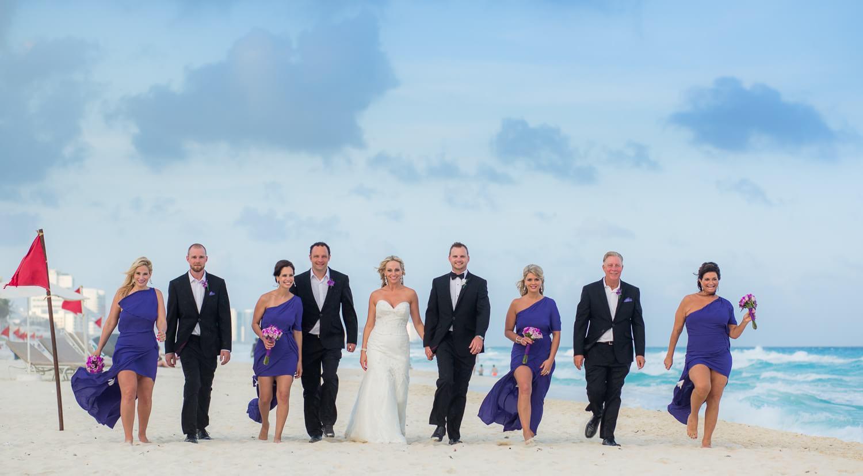 Bridal party walking down beach at cancun wedding