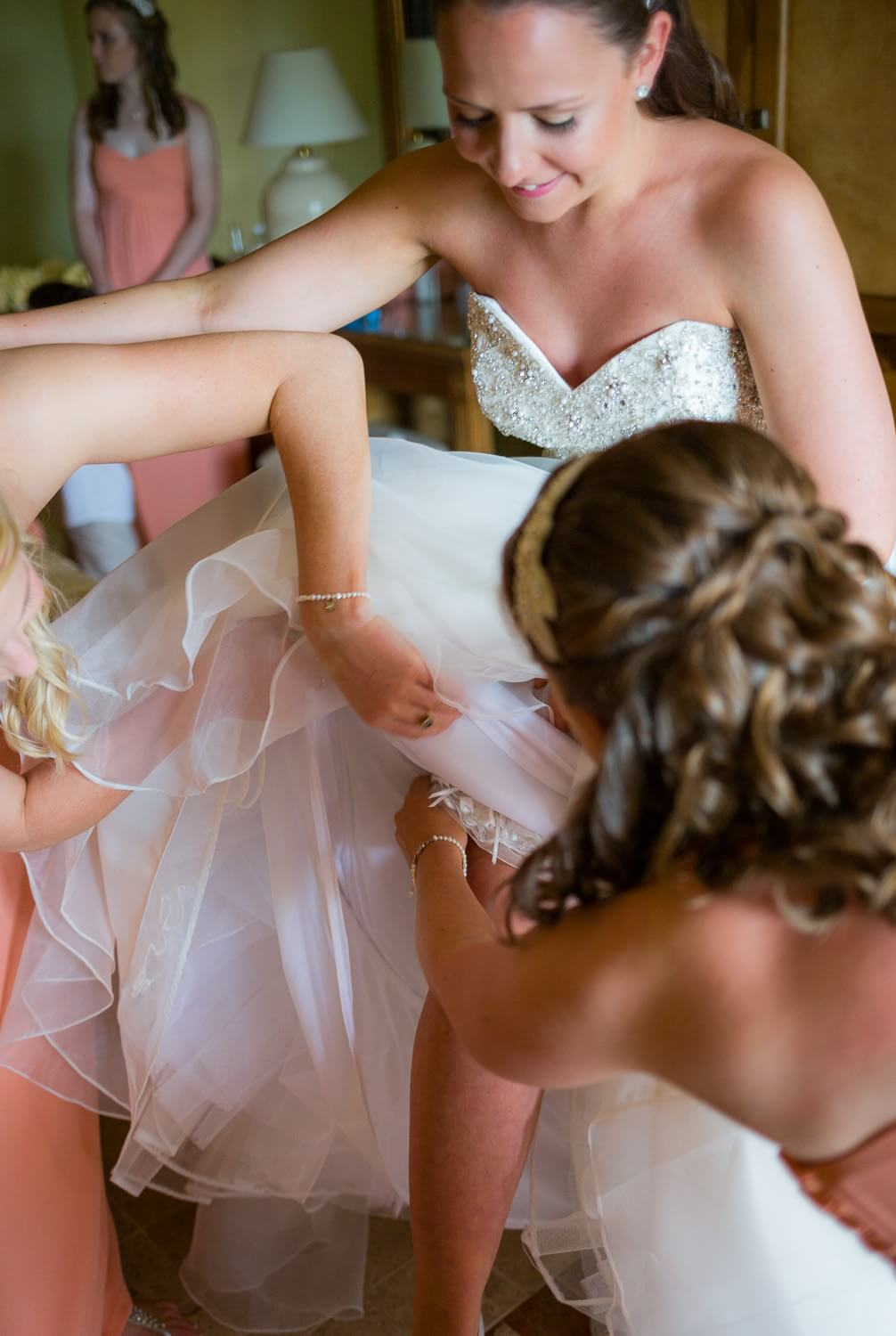 Bride putting on garter at wedding