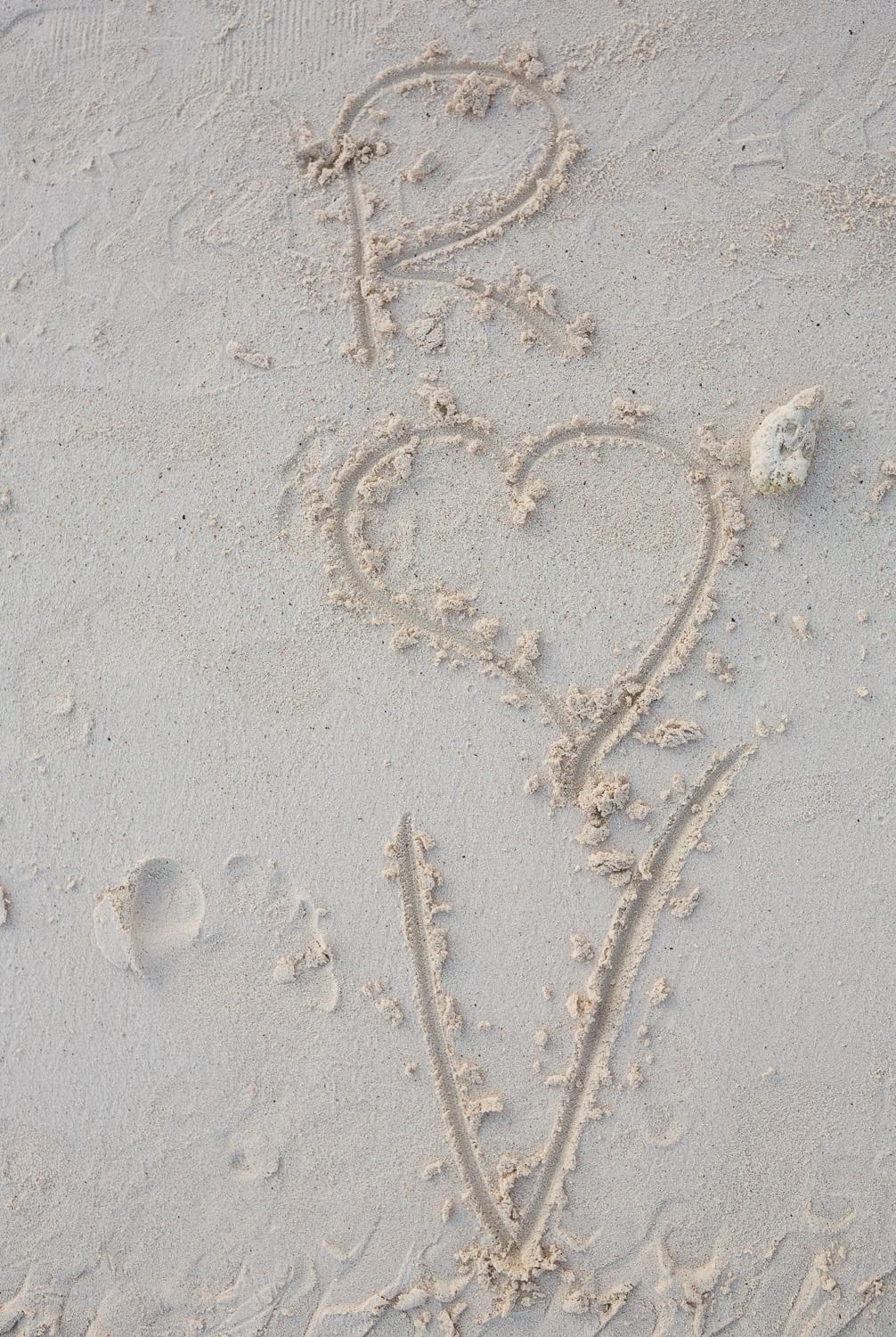 Initials in sand on beach in Mexico, wedding.