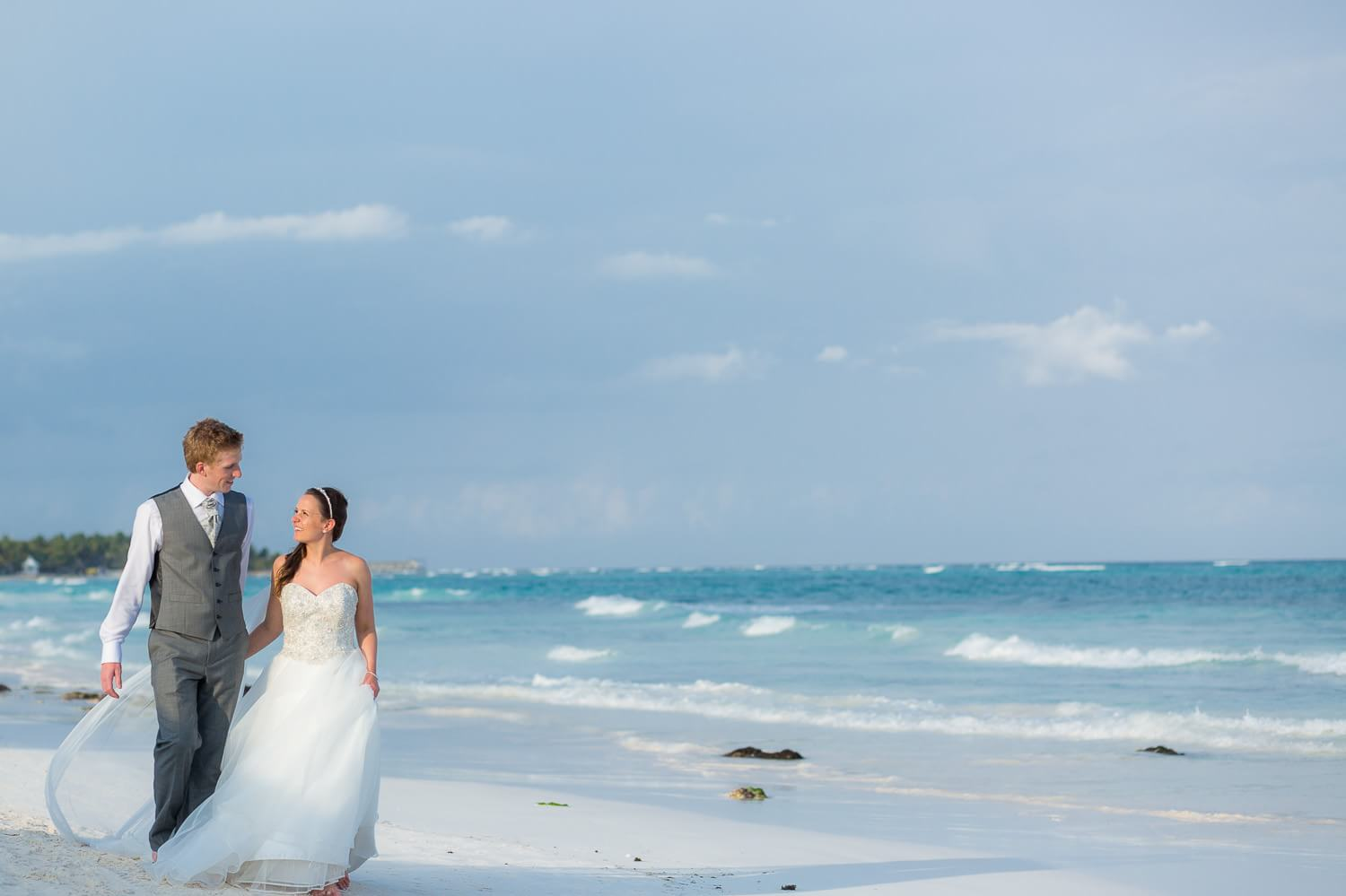 Couple walking on beach in Mexico.