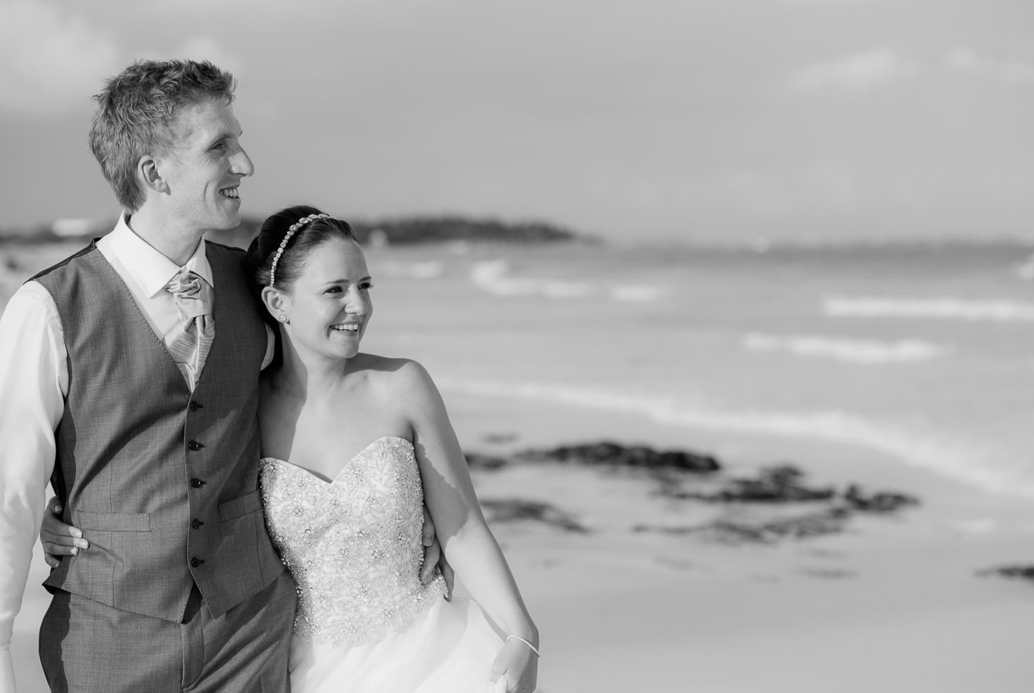 Couple walking on beach at wedding.