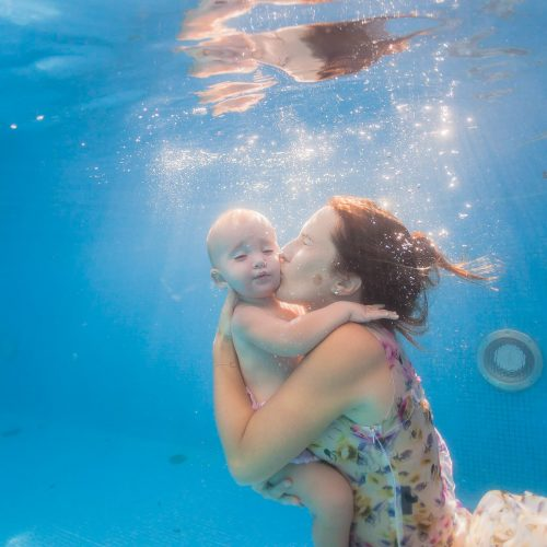 Baby underwater with mother in Mexico