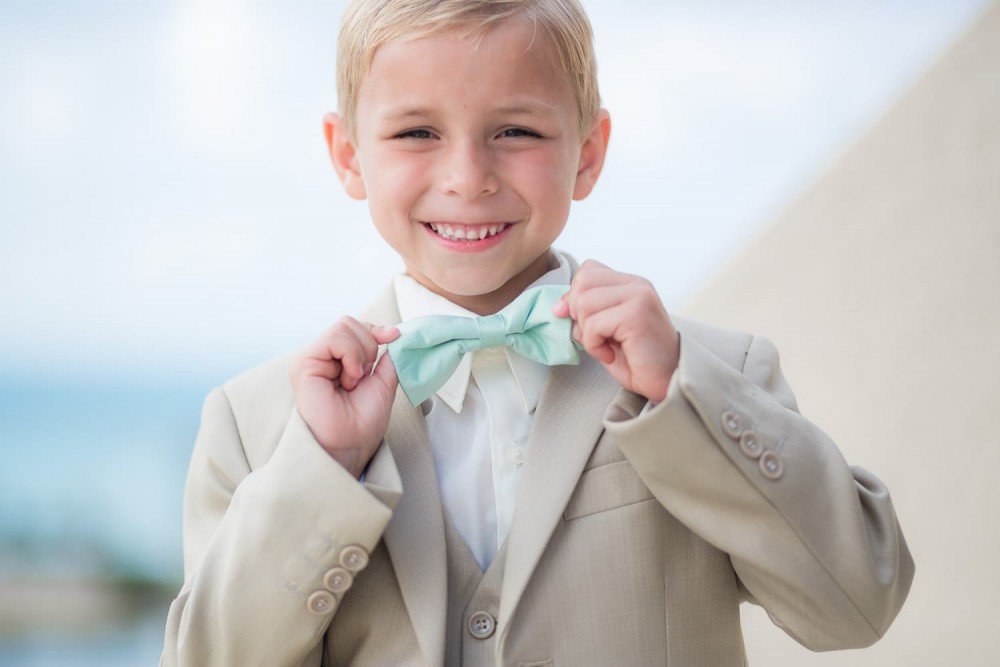 Boy holding bow tie at wedding in Cancun
