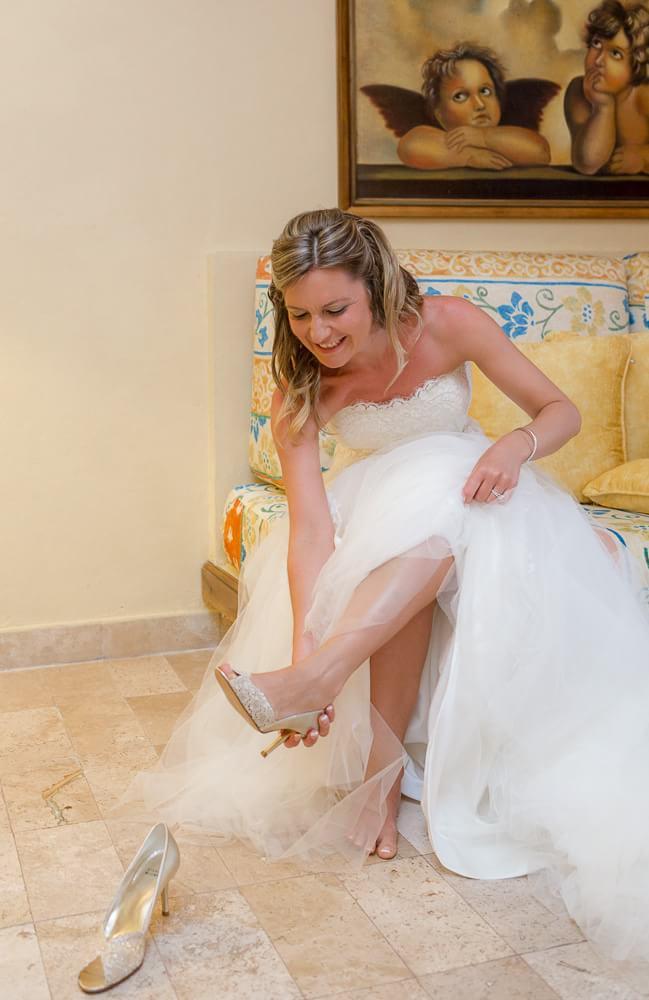 Bride putting on shoes at Iberostar Riviera Maya Wedding