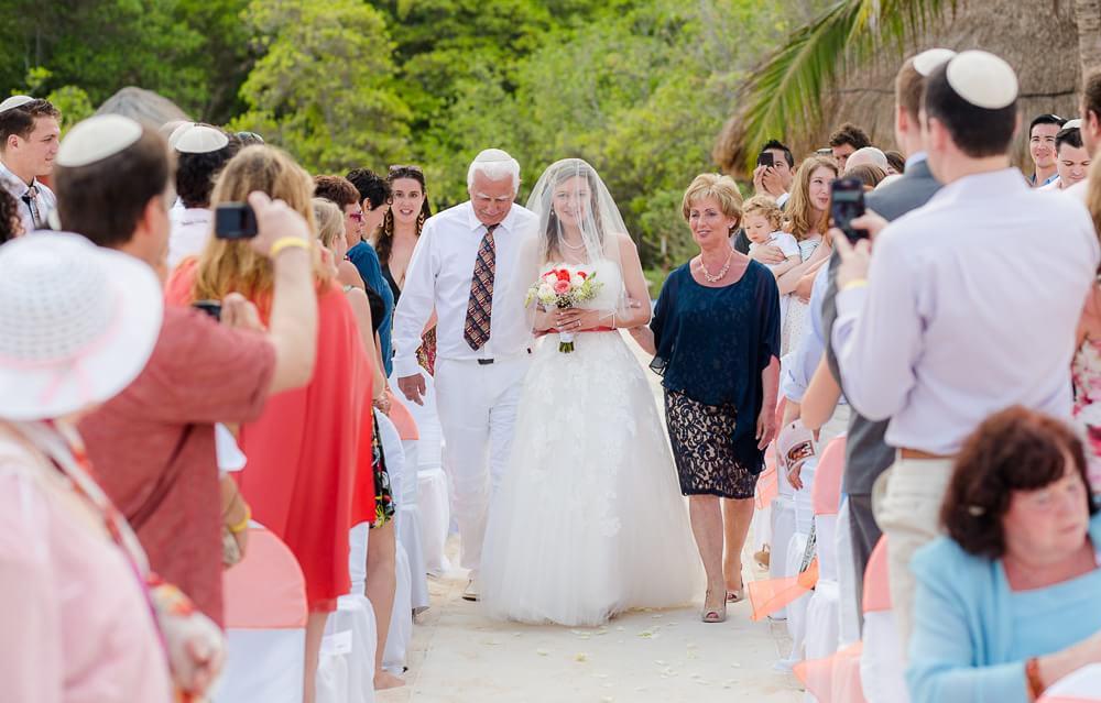 Bride walking down aisle with parents.