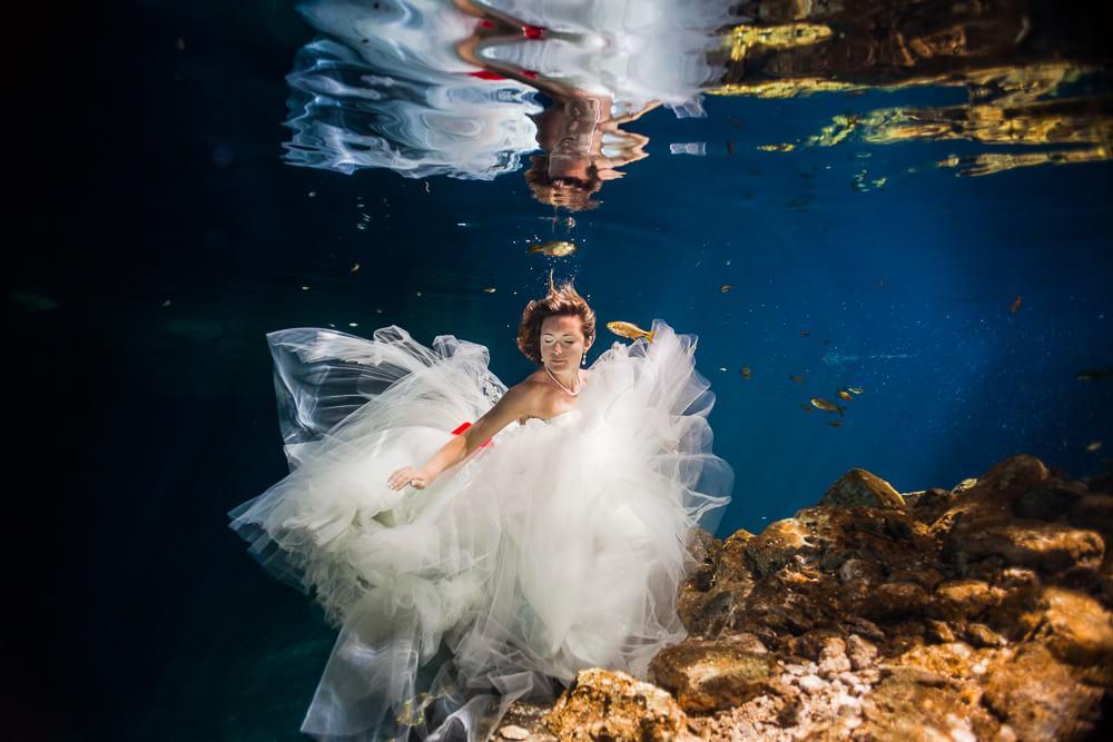 Bride in underwater trash the dress.