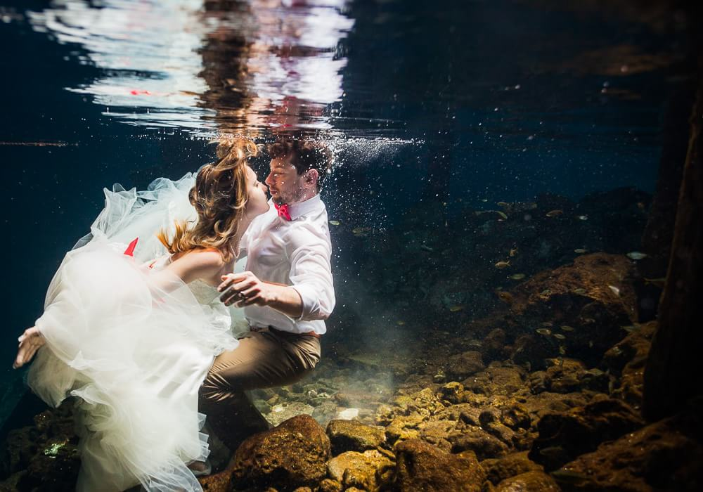 Couple in underwater cenote trash the dress