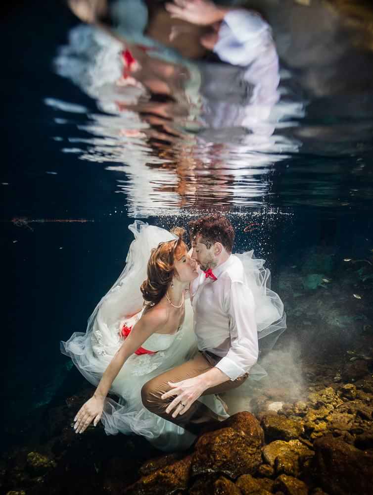 Coule kissing in Mexican cenote trash the dress