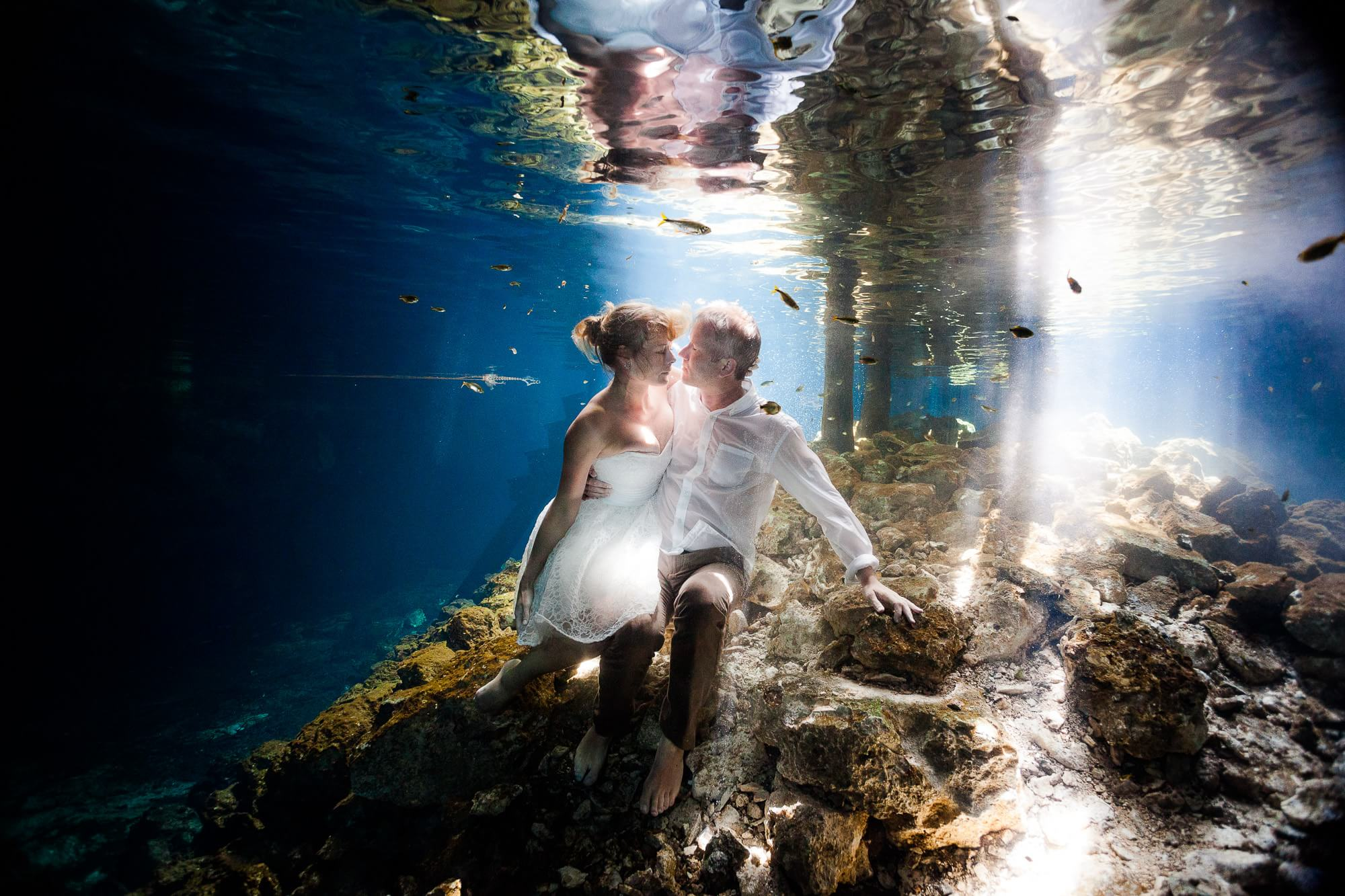 Couple underwater in Mayan Cenote trash the dress
