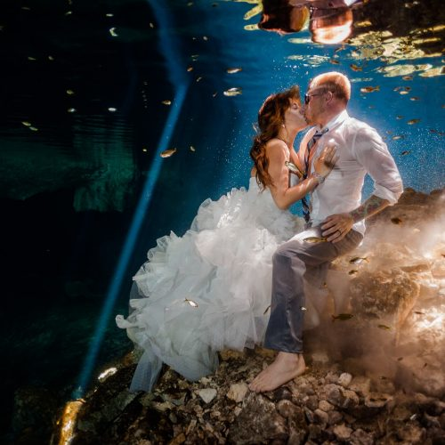 Bride and groom kissing underwater in Mayan cenote Trash the Dress session