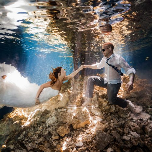 Bride and groom swimming underwater in Mayan cenote Trash the Dress session