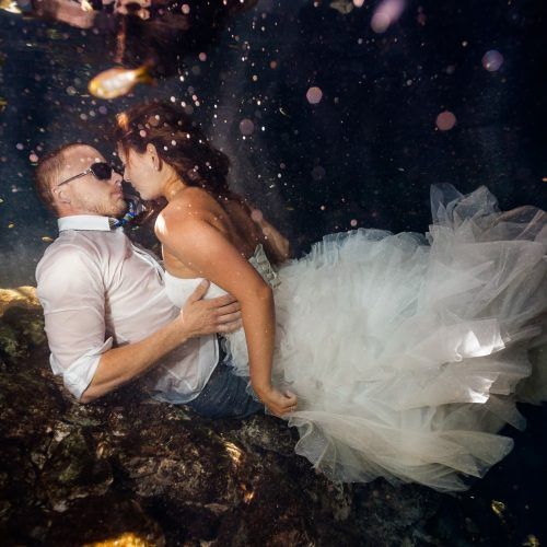 Bride and groom laying down underwater in Mayan cenote Trash the Dress session