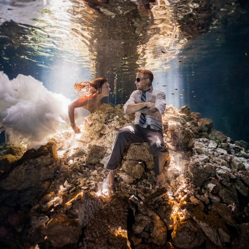 Bride swimming to groom underwater in Mayan cenote Trash the Dress session