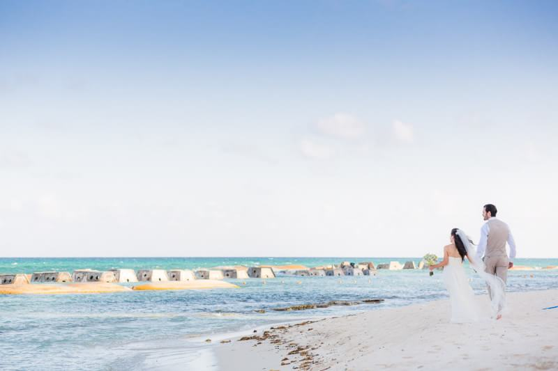 Bride and groom walking on beach at generations Riviera Maya Wedding