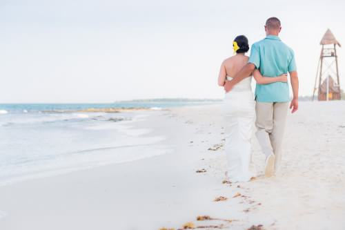 Amy and David walking down the beach at their Destination Beach Wedding at Iberostar Lindo Mexico