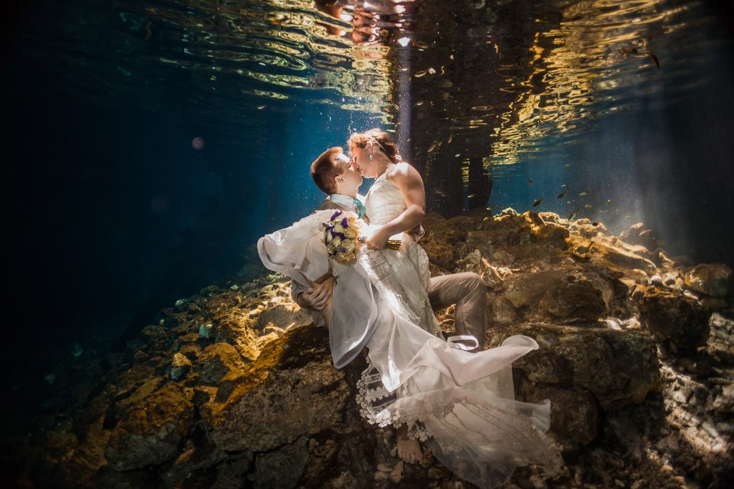Bride and groom kissing underwater in trash the dress