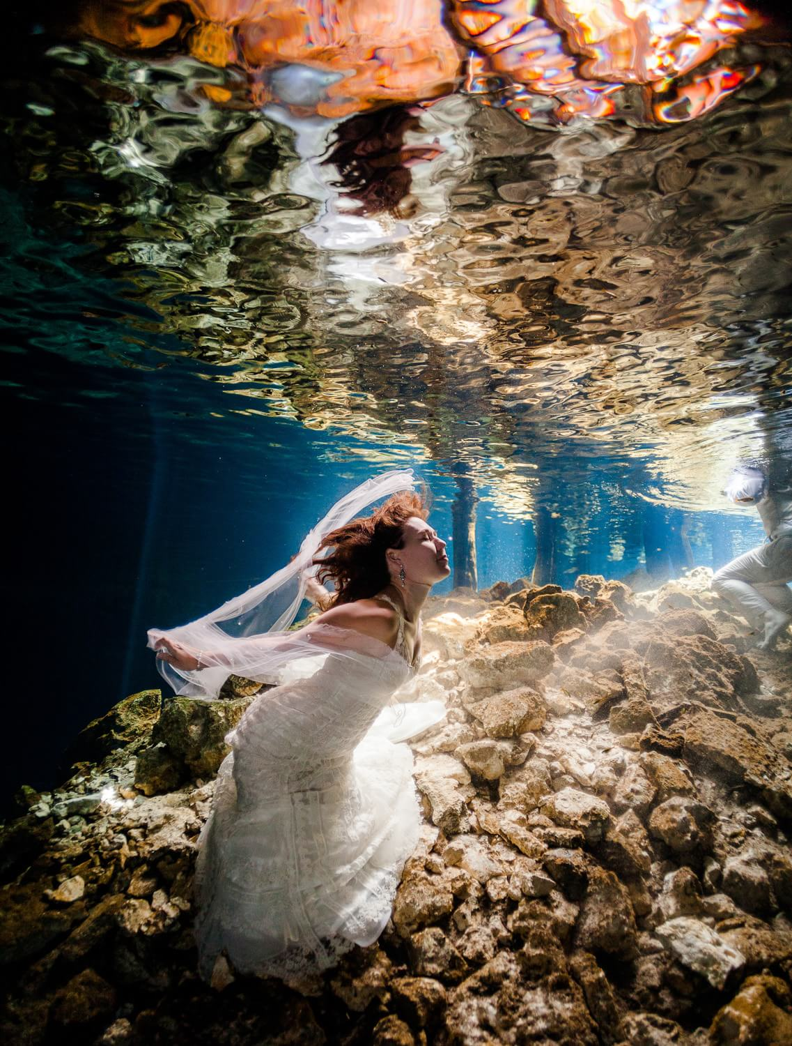 Bride with vail in underwater cenote Trash the dress wedding