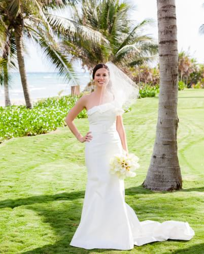 Bride wearing wedding dress on grass near beach in Riviera Maya