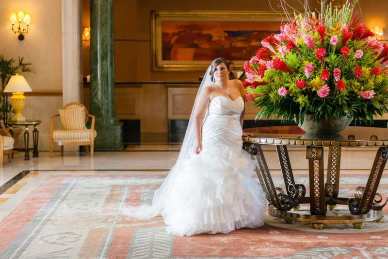 Plus sized bride wearing wedding dress in lobby of hotel