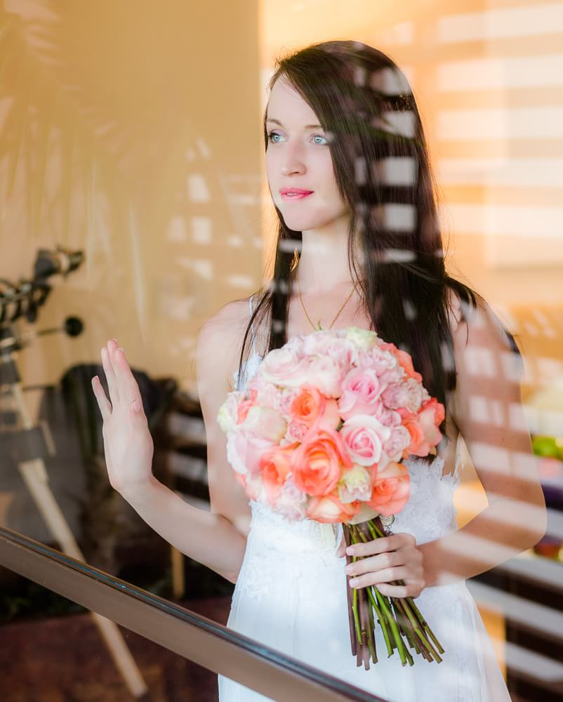 Bride looking out glass at Rosewood Mayakoba