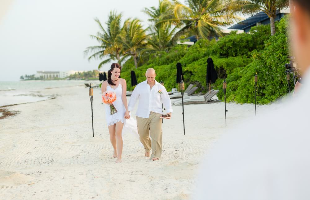 Couple walking down isle on beach