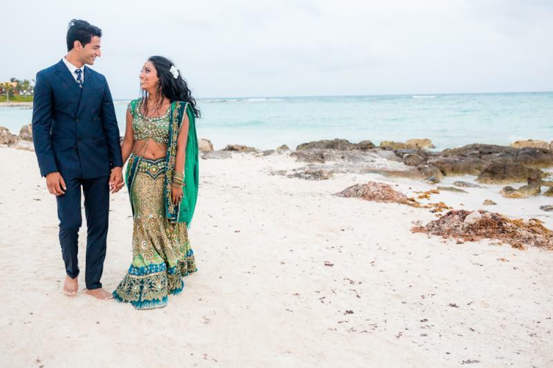 Nikita and Seth waliking down the beach at their Barcelo Riviera Maya Tropical Wedding