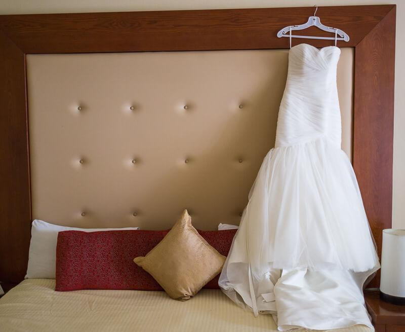 Wedding dress hanging in hotel room