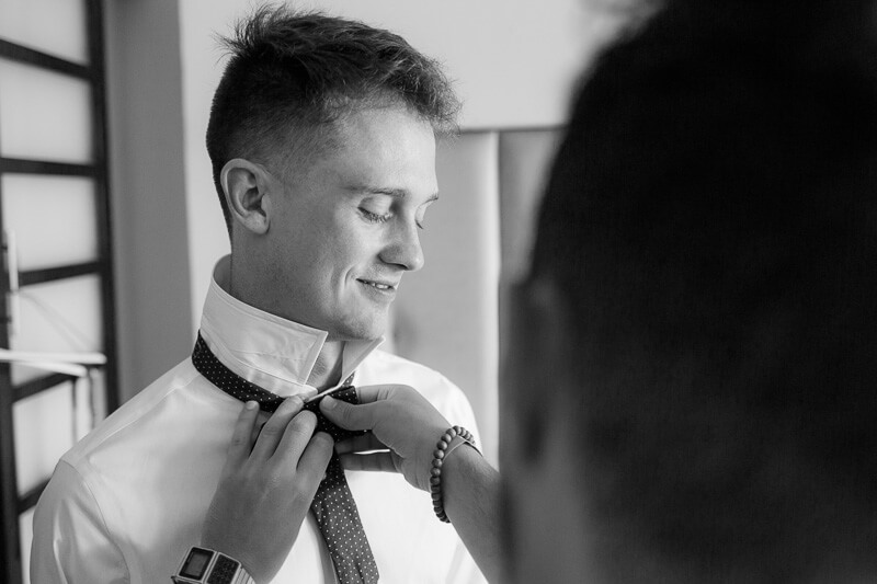 Groom doing bow tie before wedding