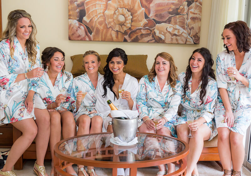 Bridesmaids laughing in robes before wedding