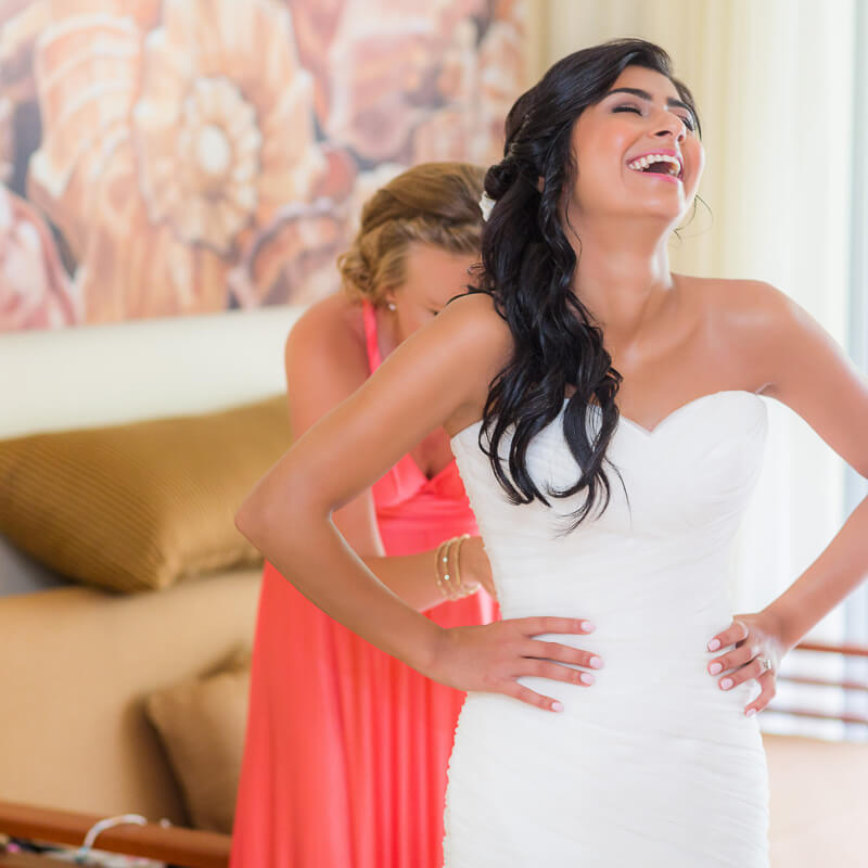 Bride laughing while having dress put on.