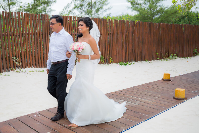 Bride and father walking down aisle towards wedding ceremony