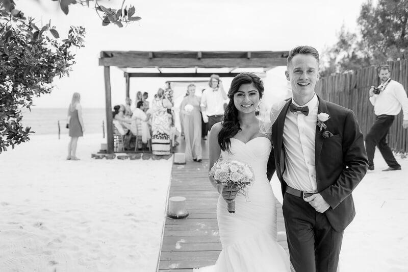 Bride and groom walking from wedding ceremony in Riviera Maya
